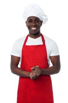 Male chef standing with his hands clasped and smiling
